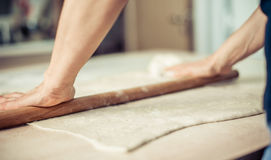 Woman rolling dough on wooden table with wooden rolling pin. Close up Royalty Free Stock Image