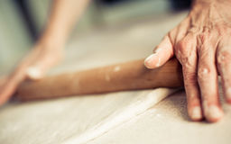 Woman rolling dough on wooden table with wooden rolling pin. Close up Royalty Free Stock Photo