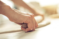 Woman rolling dough on wooden table with wooden rolling pin. Close up Stock Photos