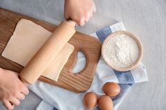 Woman rolling flaky dough on wooden board. Top view Stock Photos