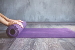 Woman rolling her mat after a yoga class Royalty Free Stock Photos