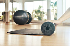 Woman rolling her mat after a yoga class Stock Photos