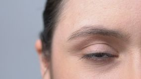 Woman rolling her red overworked eyes irritated with job, face close-up stock footage