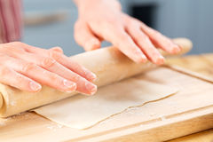 Woman rolling out dough Stock Photography