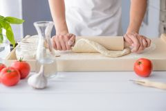 Woman rolling pizza dough using rolling pin. Stock Photography