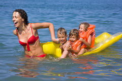 Woman rolls children on an inflatable mattress. Young woman rolls three children on an inflatable mattress in sea royalty free stock photography