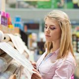 Woman with rolls of wallpaper. Young beautiful blond woman choosing among rolls of wallpaper in shop stock photography