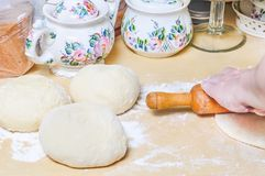 Woman rolls wheat raw dough with a rolling pin. On the flat cake Stock Photography