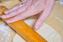 Woman rolls wheat raw dough with a rolling pin. On the flat cake Stock Photos
