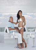 Woman Romancing With Man At Helm Of Yacht. Happy young women in bikini romancing with middle aged men at helm of yacht Stock Image