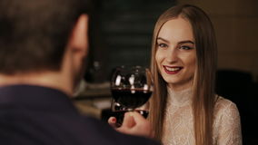 Woman in a romantic dinner toasting with wine. Young happy couple romantic date drink glass of red wine at restaurant, celebrating valentine day stock footage