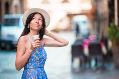 Woman in Rome with coffee to go on vacation travel. Smiling happy caucasian girl having fun laughing on Italian sidewalk Royalty Free Stock Image
