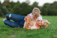 Woman romps with her son on the grass Royalty Free Stock Image
