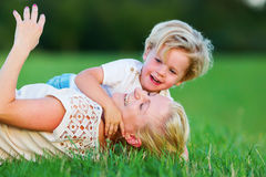 Woman romps with her son on the grass Royalty Free Stock Photo