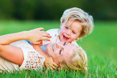 Woman romps with her son on the grass. Picture of a women who romps with her son on the grass Stock Images