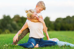 Woman romps with her son on the grass Stock Images