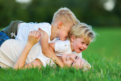 Woman romps with her two sons on the grass Stock Photos