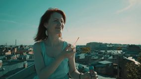 Woman on the roof. Girl walking on the roof and blowing bubbles stock video footage