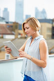 Woman On Roof Terrace Using Digital Tablet Royalty Free Stock Photo