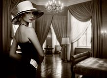 Woman in a room. Beautiful woman in hat in luxury room Royalty Free Stock Images