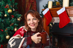 Woman in the room with fireplace and Christmas decorations Stock Photography