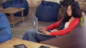 Woman in the room with modern interior typing on laptop. Young asian girl chatting in social net on computer use wifi. Student or worker work with office stock video footage