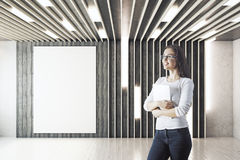 Woman in room with poster. Cheerful young businesswoman standing in unfurnished hipster interior with empty poster on wall. Mock up, 3D Rendering Stock Photos