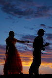 Woman with a rope around a cowboy silhouette Stock Images