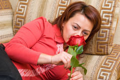 Woman with rose. Rests upon sofa Stock Photography