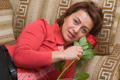 Woman with rose. Rests upon sofa Stock Image