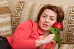 Woman with rose. Rests upon sofa Royalty Free Stock Photo