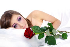 Woman with rose in bed Stock Photos