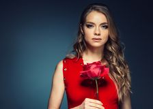 Woman with rose flower. Beauty female portrait with beautiful rose flower and salon hairstyle over gay blue background blonde hair. And red dress. Studio shot stock photo