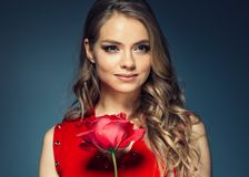 Woman with rose flower. Beauty female portrait with beautiful rose flower and salon hairstyle over gay blue background blonde hair. And red dress. Studio shot stock photos