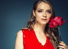 Woman with rose flower. Beauty female portrait with beautiful rose flower and salon hairstyle over gay blue background blonde hair. And red dress. Studio shot royalty free stock image