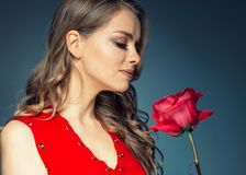 Woman with rose flower. Beauty female portrait with beautiful rose flower and salon hairstyle over gay blue background blonde hair. And red dress. Studio shot stock image