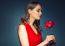 Woman with rose flower. Beauty female portrait with beautiful rose flower and salon hairstyle over gay blue background blonde hair. And red dress. Studio shot stock photography