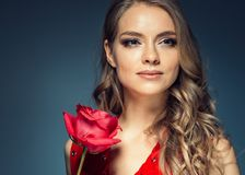 Woman with rose flower. Beauty female portrait with beautiful rose flower and salon hairstyle over gay blue background blonde hair. And red dress. Studio shot royalty free stock images