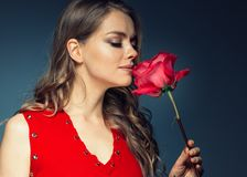 Woman with rose flower. Beauty female portrait with beautiful rose flower and salon hairstyle over gay blue background blonde hair. And red dress. Studio shot royalty free stock photography