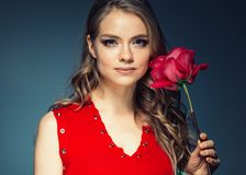 Woman with rose flower. Beauty female portrait with beautiful rose flower and salon hairstyle over gay blue background blonde hair. And red dress. Studio shot royalty free stock photos
