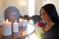 Woman with rose and funerary urn at church Stock Images