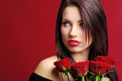 Woman with a  rose over red background Royalty Free Stock Image