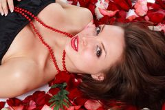 Woman on rose petals. Attractive young woman on rose petals royalty free stock photo