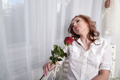 Woman with a rose sitting on a chair near the window Stock Photography