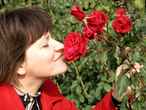 Woman and roses. Portrait of woman sniffing at a red roses Stock Photography