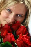 Woman with Roses. Portrait of young woman with bouquet of red roses royalty free stock image