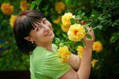 Woman and roses. Beautiful woman standing near a bush with roses blossomed Stock Image