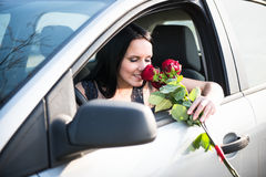 Woman with roses in car Royalty Free Stock Photos