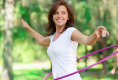 Woman rotates hula hoop in forest Stock Photography