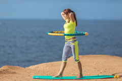 Woman rotates hula hoop on summer beach Royalty Free Stock Photography